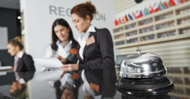 Hotel concierges in the background with a small bell on a countertop in the foreground.