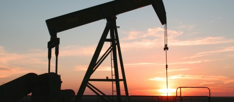 A pump jack in an oil field at dusk