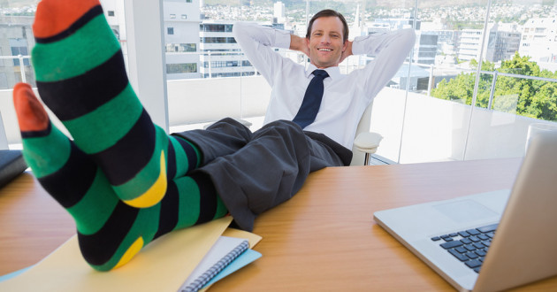 A businessman wearing funny socks at his desk in an office.