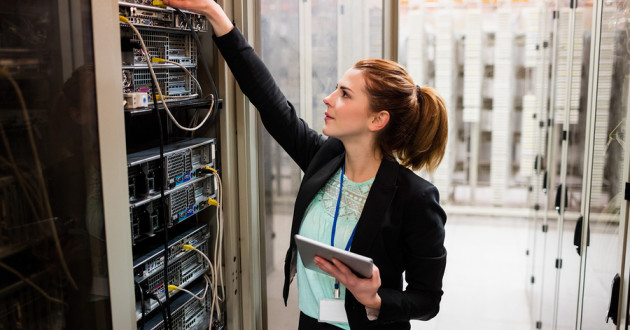 A female IT professional working in a server room.