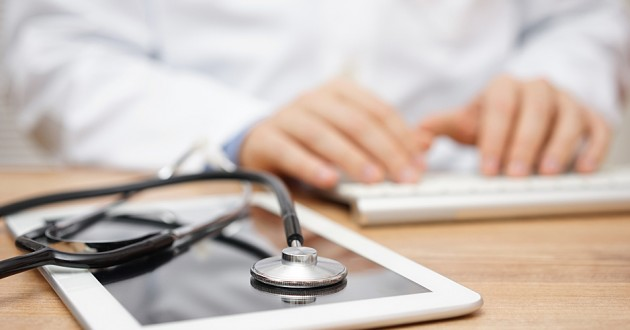 A stethoscope lying on top of a digital tablet and a health care professional typing in the background.