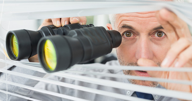 A man peering through window blinds using binoculars.