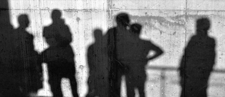 Multiple shadows of people on a white concrete wall.