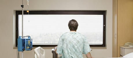 A man seen from behind in a hospital gown sitting on his hospital bed, looking out the window