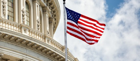 An American flag waving in front of the U.S. Capitol building.