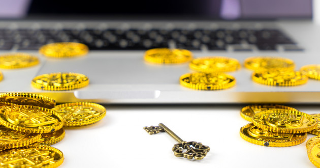 Laptop covered in bitcoins and one small silver key.