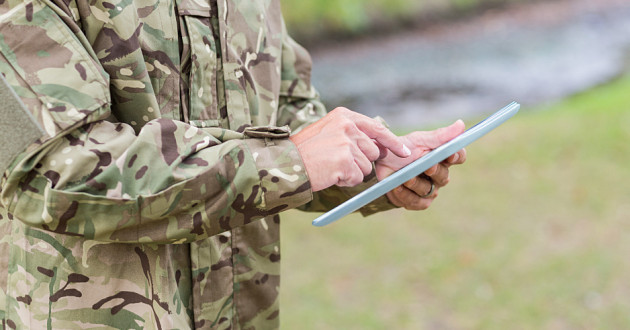 A soldier using a digital tablet outdoors.