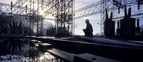 A worker crouching under an electrical structure.