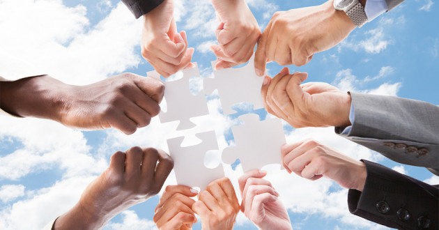 Many hands joining four pieces of a jigsaw puzzle against a backdrop of clouds and blue sky.