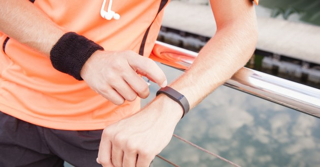 A runner using a fitness device to track steps.