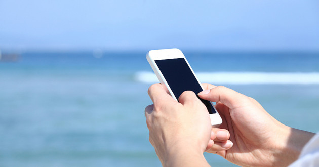 A person using a smartphone near the ocean.