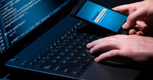 A person typing on a laptop while entering a password into a smartphone.