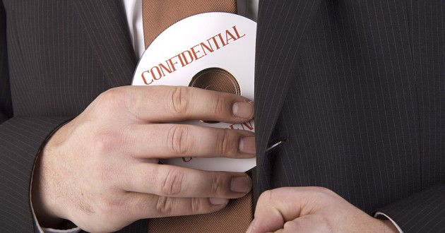 "A man in a business suit hiding a compact disc labeled ""confidential."""