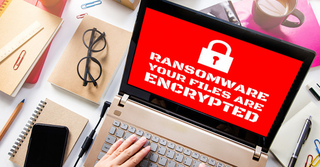 A laptop screen displaying a ransomware message.