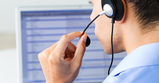 A call center employee using a computer while talking through a headset.