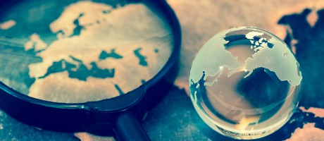 A magnifying glass and a crystal globe on a world map.