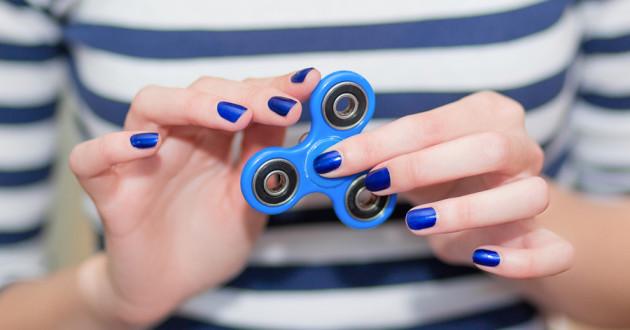 A woman holding a blue fidget spinner.