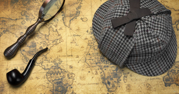 Sherlock Holmes hat, magnifying glass and smoking pipe resting on a map.