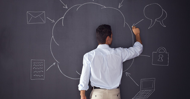 A man drawing a diagram of a cloud computing concept on a blackboard.
