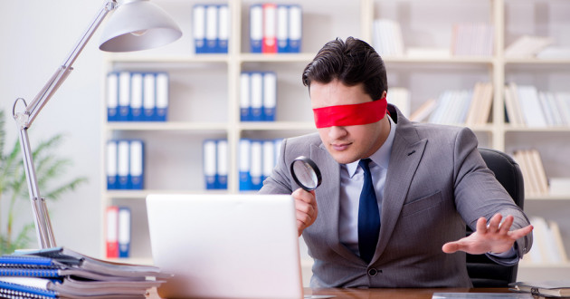 A businessman holding a magnifying glass while blindfolded.