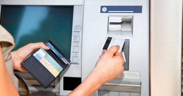 A hand inserting a payment card into an ATM machine.