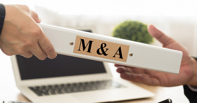 """Two hands exchanging a binder labeled """"M&A."""""""