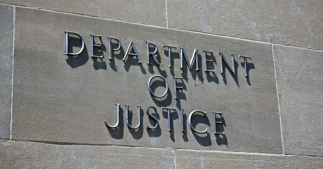 "A sign on the outside of a building reading ""Department of Justice."""