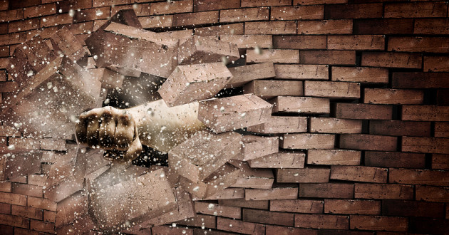 A hand punching through a brick wall.