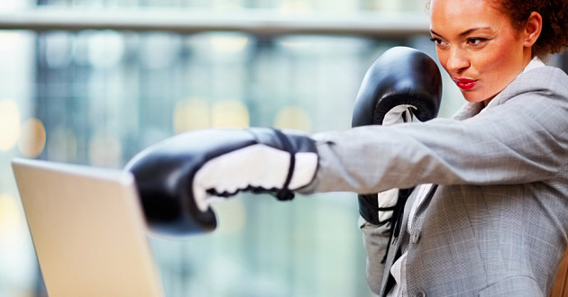 A businesswoman wearing boxing gloves and punching a laptop screen.