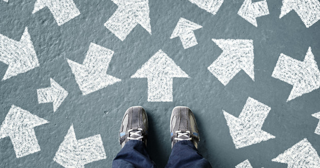 A person standing on a paved surface flecked with white arrows.