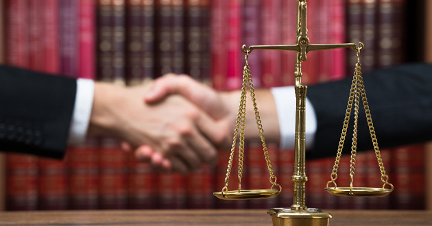 A justice scale on a wooden table with two arms shaking hands in the background.