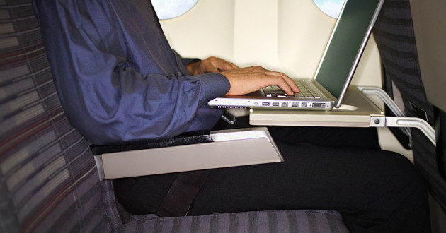 A man in business attire typing on a laptop while sitting on an airplane.