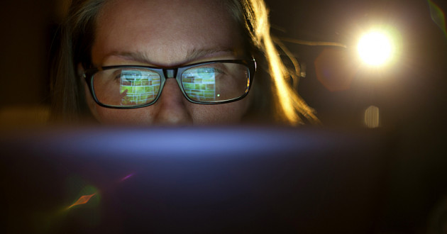 A digital tablet screen reflecting off a woman's glasses.