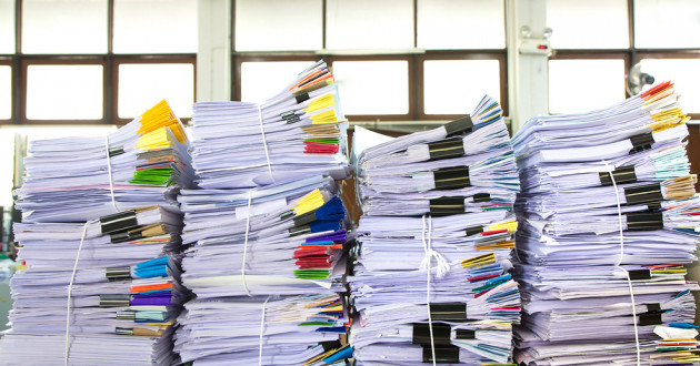 Stack of business papers piled on a desk.
