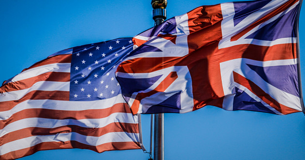 An American flag and a Union flag waving in the wind.