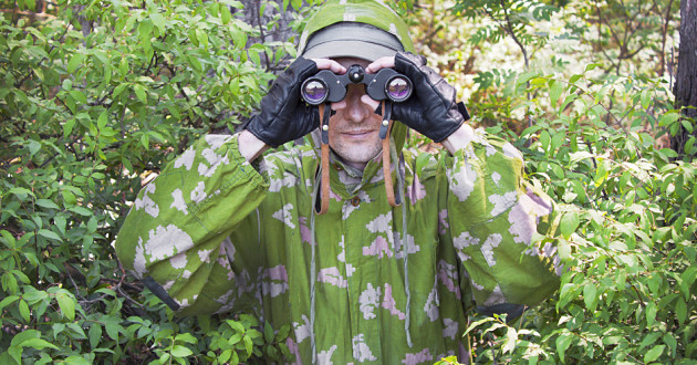 A man wearing a camouflage jacket and using binoculars in a wooded area.