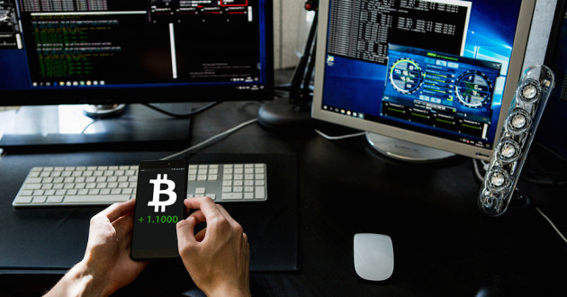 Person holding a phone with the Bitcoin exchange rate on the screen in front of computer monitors.