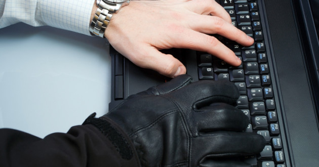 A person typing while wearing a black glove on one hand.