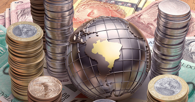 A metal globe surrounded by Brazilian currency.