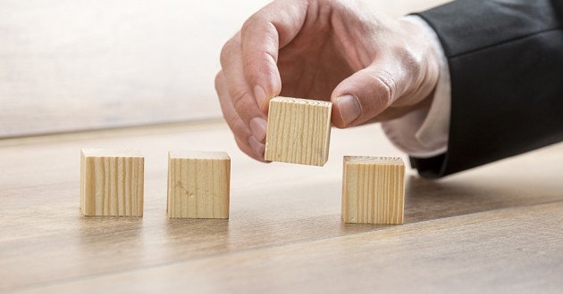A hand placing wooden blocks in a row.
