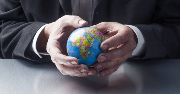 A person holding a  minute globe.