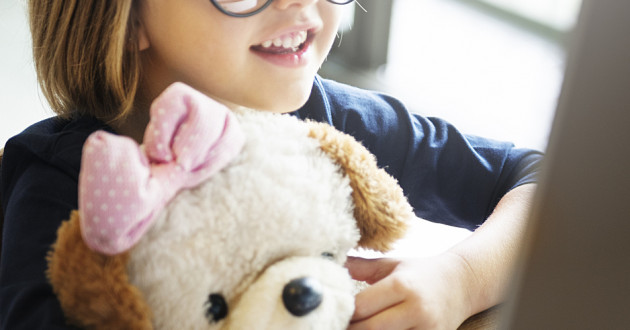 A child playing with a stuffed animal while using a laptop.