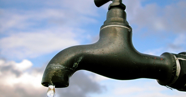A leaking spigot against a backdrop of clouds and blue sky.