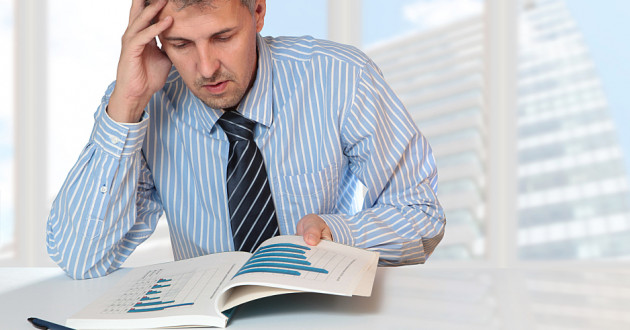 A businessman reading a report with a confused expression.