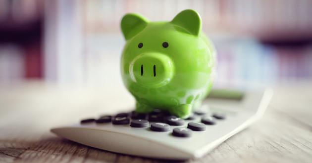 A green piggy bank sitting on a calculator.