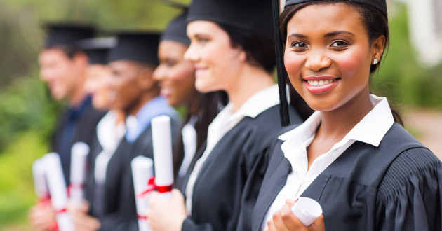 Students standing in a row wearing graduation gowns and holding rolled-up degrees.