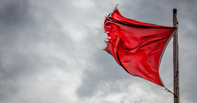 A frayed red flag waving in the wind.