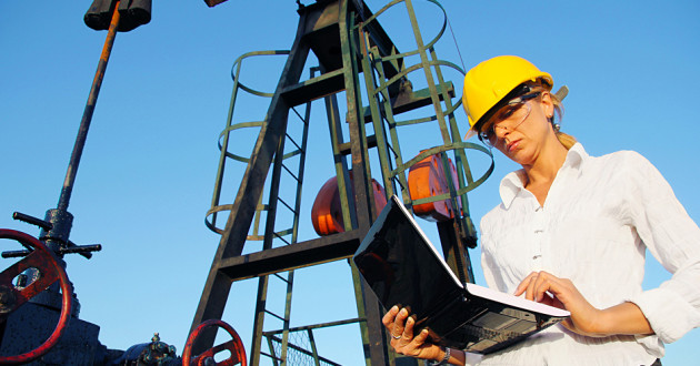 A woman using a laptop next to an oil rig.
