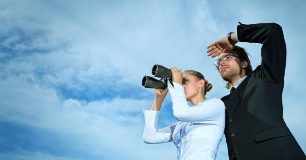 Two businesspeople looking at clouds through binoculars.
