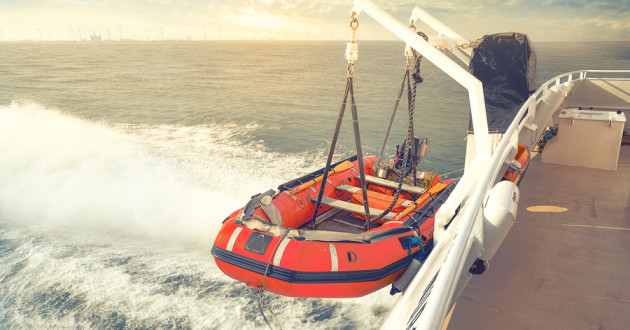 A life raft suspended over the ocean from a larger vessel.